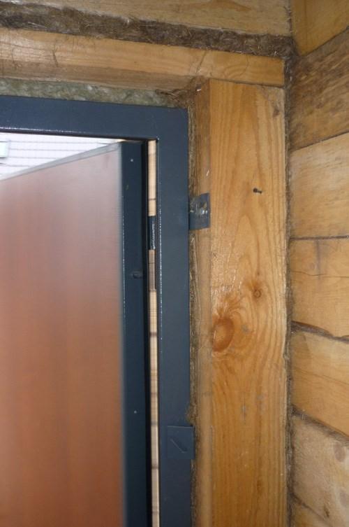 Коробка металлической двери в деревянном доме