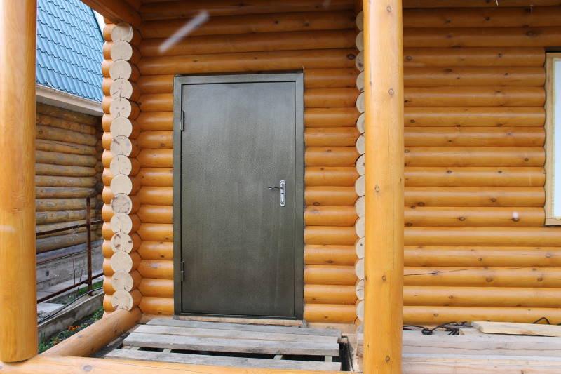 Железная дверь в доме из оцилиндрованного бревна