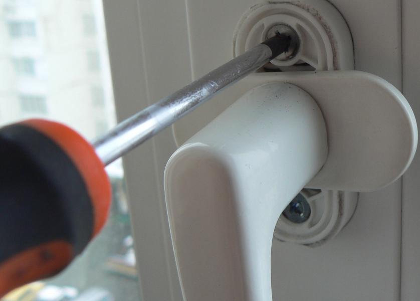 Закручивание крепежных винтов пластиковой ручки двери
