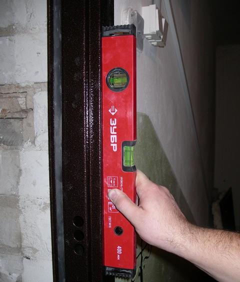 Проверка уровнем ровности установки металлической двери